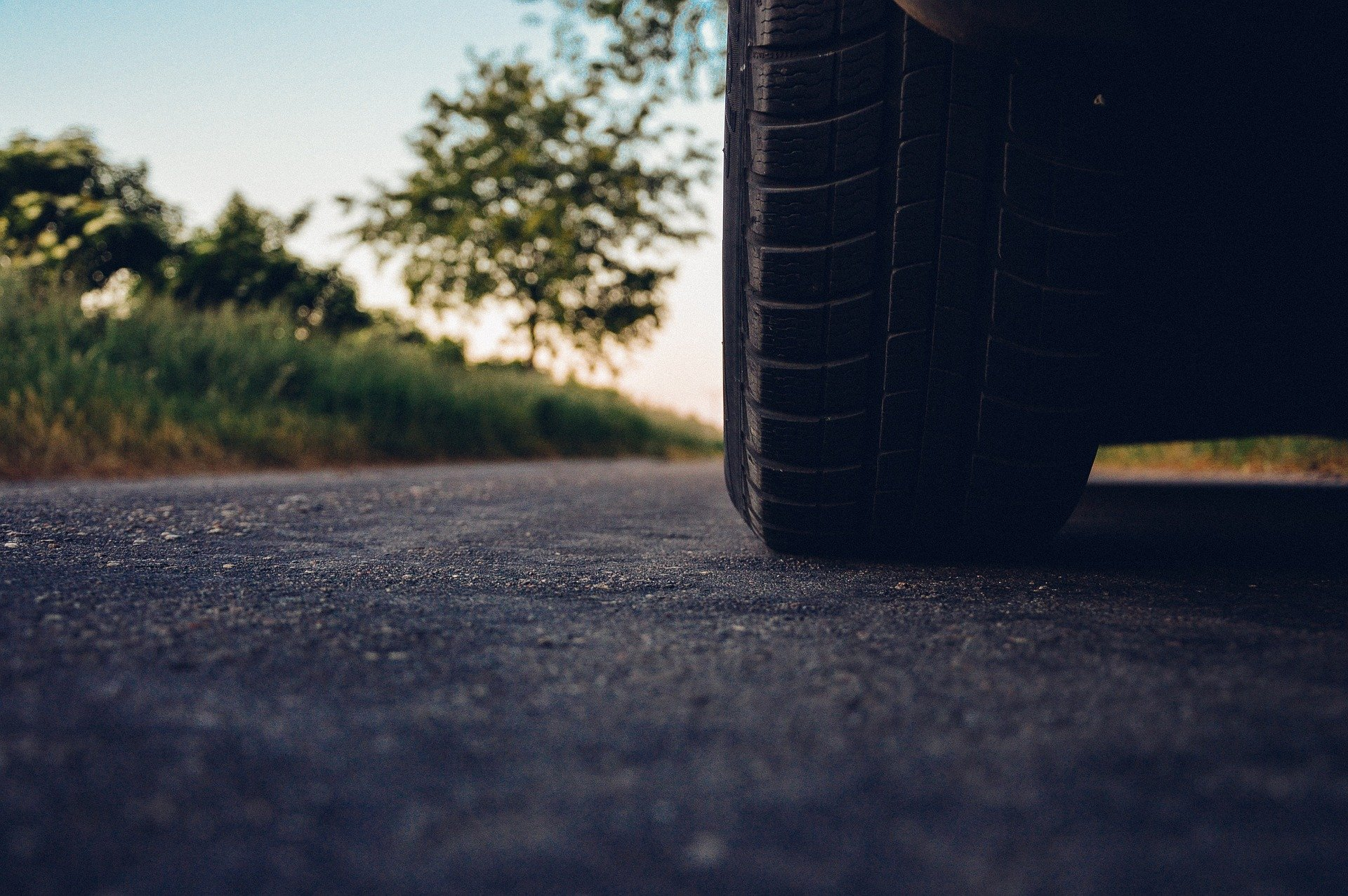 low-angle-view-of-car-tire-on-asphalt-road-with-grass-and-tree-in-background