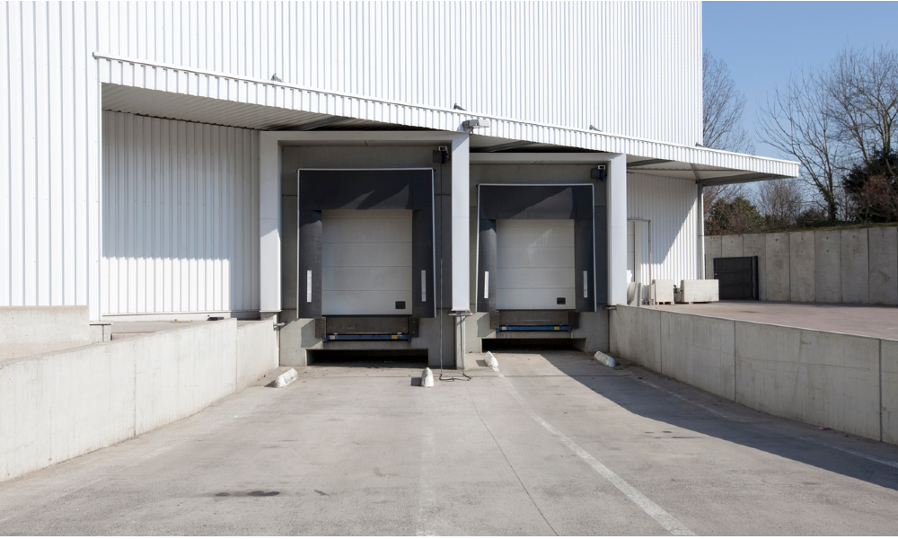 Two trucks are parked in a dual concrete loading dock in an industrial building.