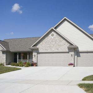 upscale stone home with a paved driveway and a three car garage. ** Note: Slight graininess, best at smaller sizes